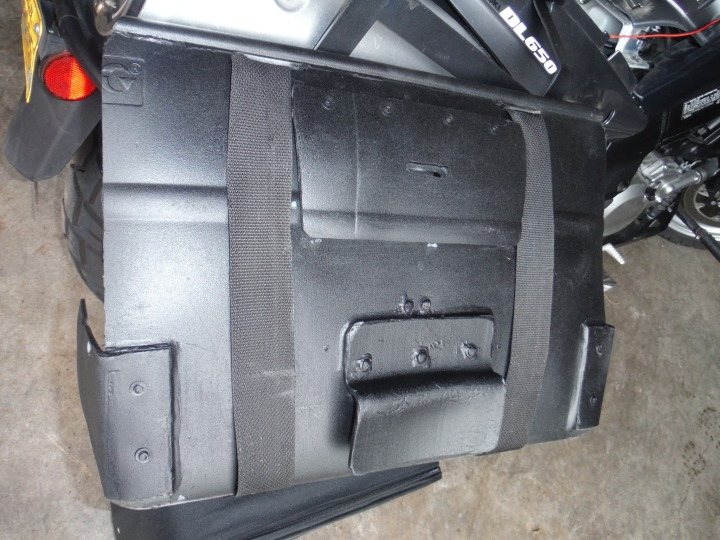 "Showing brackets on the back that slide onto rack. Note the slot in the upper bracket for ""L"" bracket to slide through and secure the luggage rack to the metal rack. Note that everything is riveted and hot glued on."